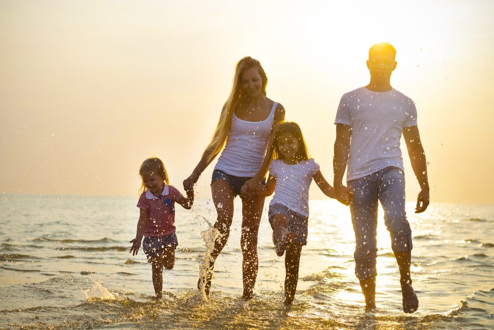 Picture of a Happy Young Family Having Fun Running on Beach at Sunset.